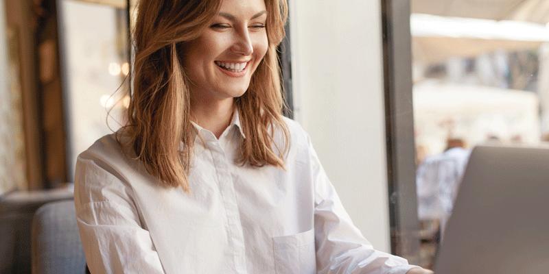 A user interface designer smiling at her laptop screen