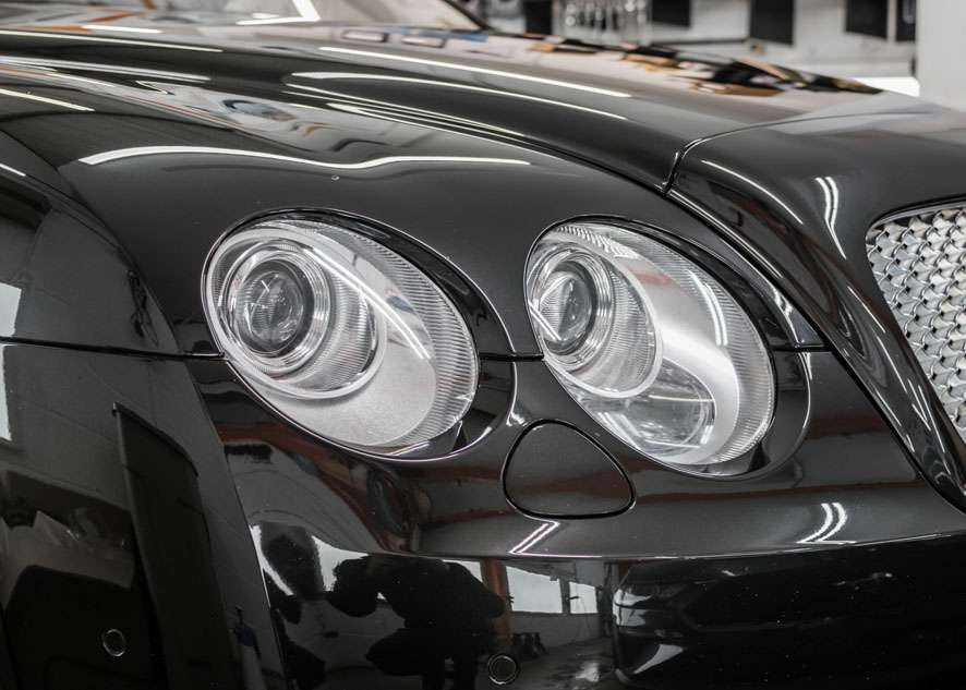 Close up shot of two Bentley Flying Spur car headlights with fog/cloudiness removed after headlight restoration