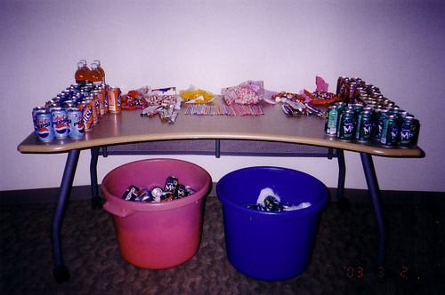 The sugar table at the first Animarathon. Soda pops adorn the sides with snacks in the center of the table. Two buckets of additional soda are under the table.