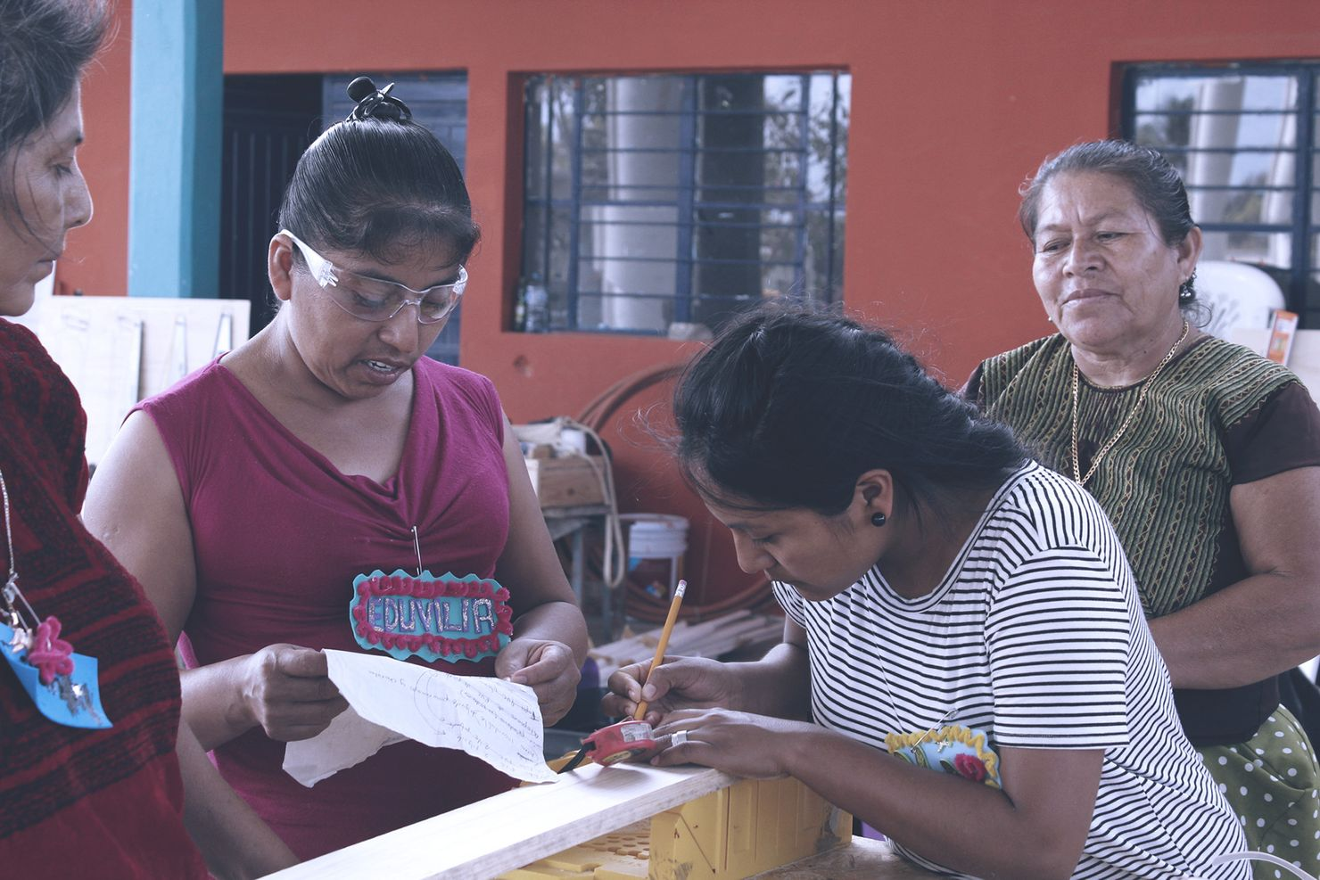 two oaxacan women collaborate to build something (one is marking a measurement on a piece of wood) while a third woman watches