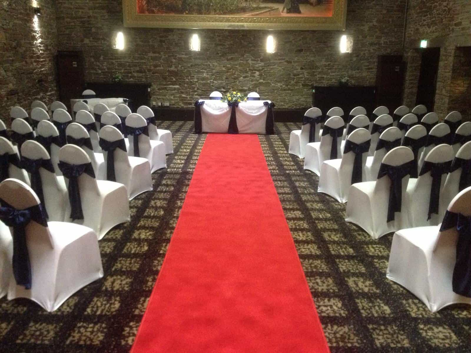 Wedding ceremony in a dark room with a red aisle runner