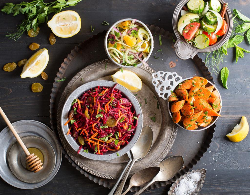 colorful vegetable salads in mismatched bowls