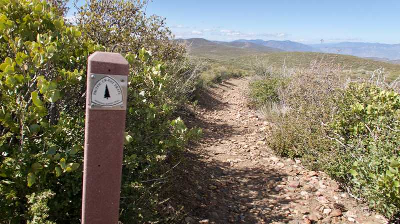 Rocky trail with trail marker on post