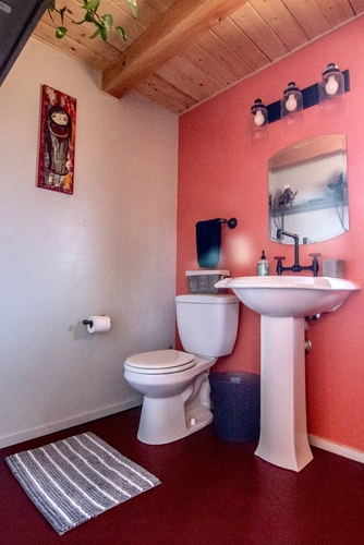 Bathroom area, with full size toilet and sink.