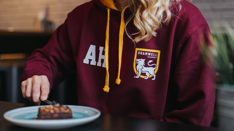 A blonde student in a burgundy leavers hoodie with gold hood and toggles, eating a brownie