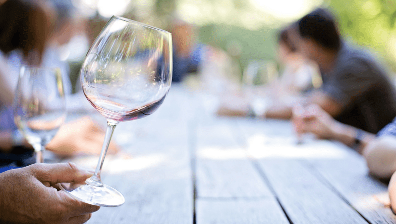 Wine glass is held up above table outside at winery, people tasting wines on long table with greenery in background #business