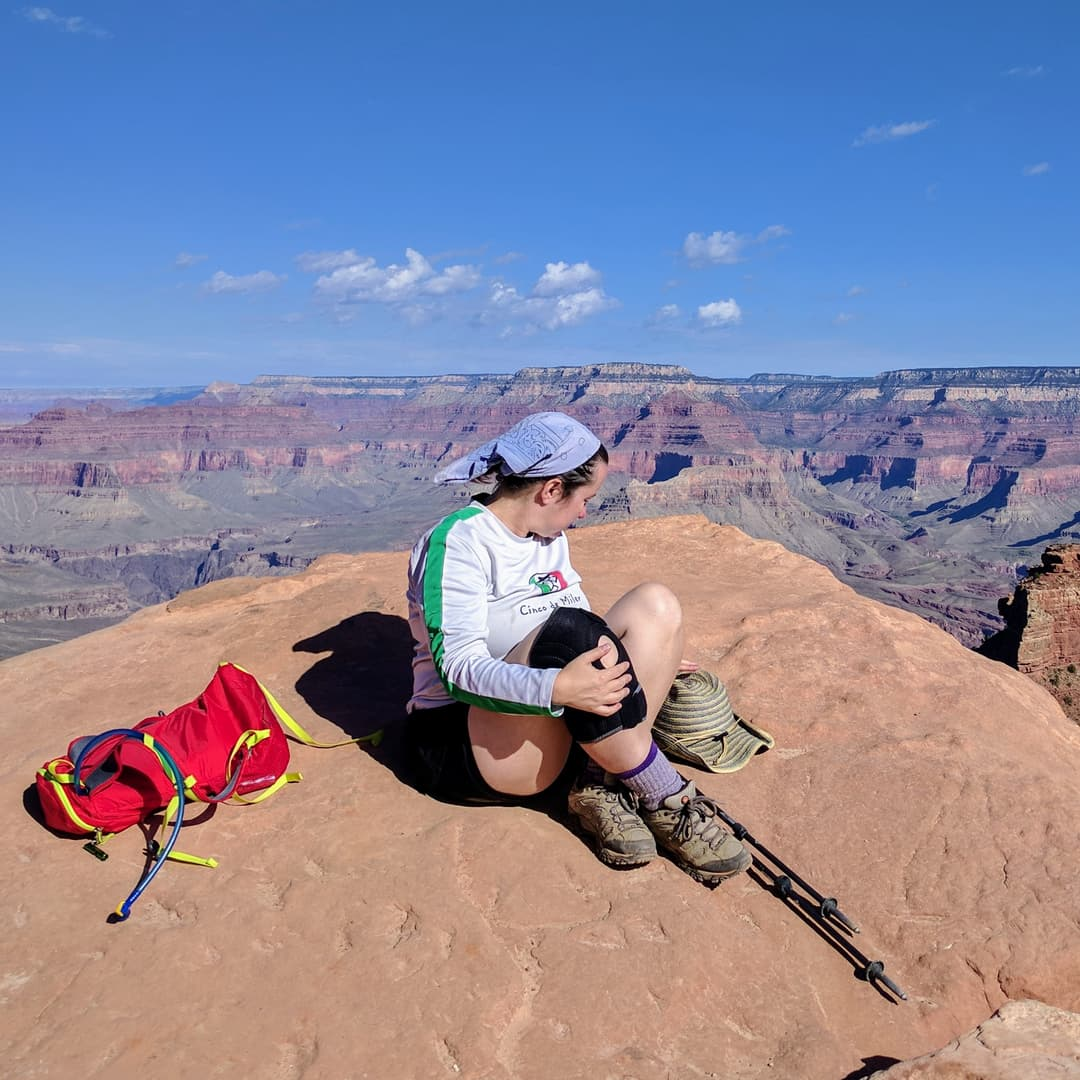 Len sitting on a large flat red sandstone rock. Beyond her, a mesa-like 'temple', and further still the floor of the Grand Canyon itself.