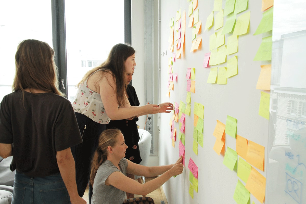 A group of colleagues sticking Post-its on a wall as part of a design thinking workshop