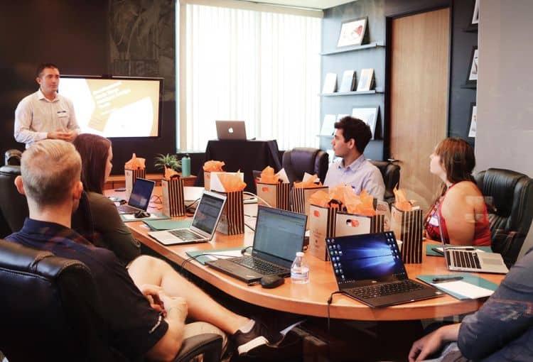PowerPoint Präsentation auf Bildschirm während einer Firmenschulung mit Laptops