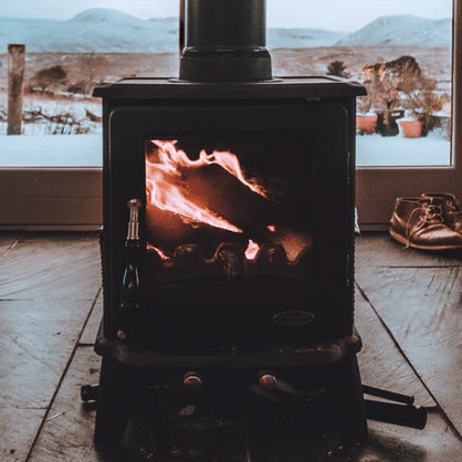 A black wood/log burning stove in the middle of a room, with mountains in the background (seen through the glass doors), from Michael Shannon of Unsplash.