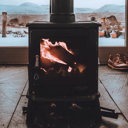 Un poêle à bois / bûches noir au milieu d'une pièce, avec des montagnes en arrière-plan (vu à travers les portes vitrées), de Michael Shannon de Unsplash.