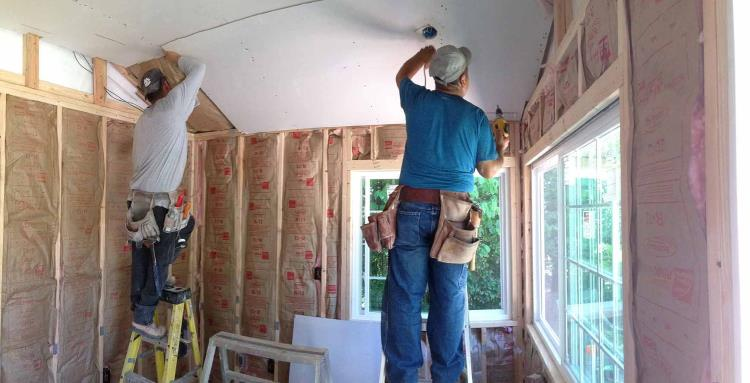 Lots of R-13 insulation fibreglass roll insulation in-between the vertical wood studs, as can be seen on 3 different walls, from Tuff Shed.