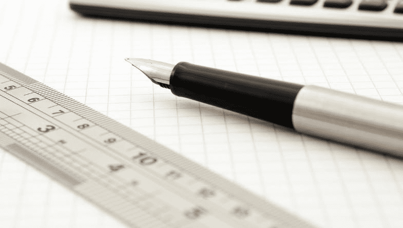 A ruler and pen lie on lined paper next to a laptop that is open to explain how to measure key performance indicators for businesses, advisors and accountants. #KPI
