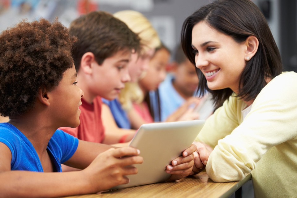 A woman, smiling and looking at a child, who is holding a tablet
