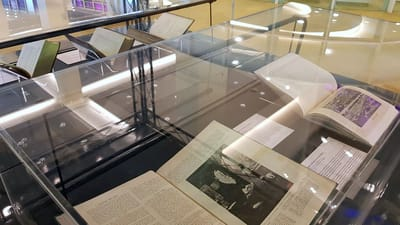 Photo of the showcases, with books inside. They are opened up, and the book closest to the foreground has an image of Sir Stamford Raffles. The book next to it has a photograph of a crowd.