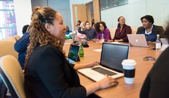 Kursteilnehmer mit Laptops an Tisch während einer Firmenschulung