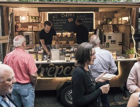 Schick gekleidete Menschen genießen ihre Crêpes vor einem Food Truck bei Hochzeitscatering