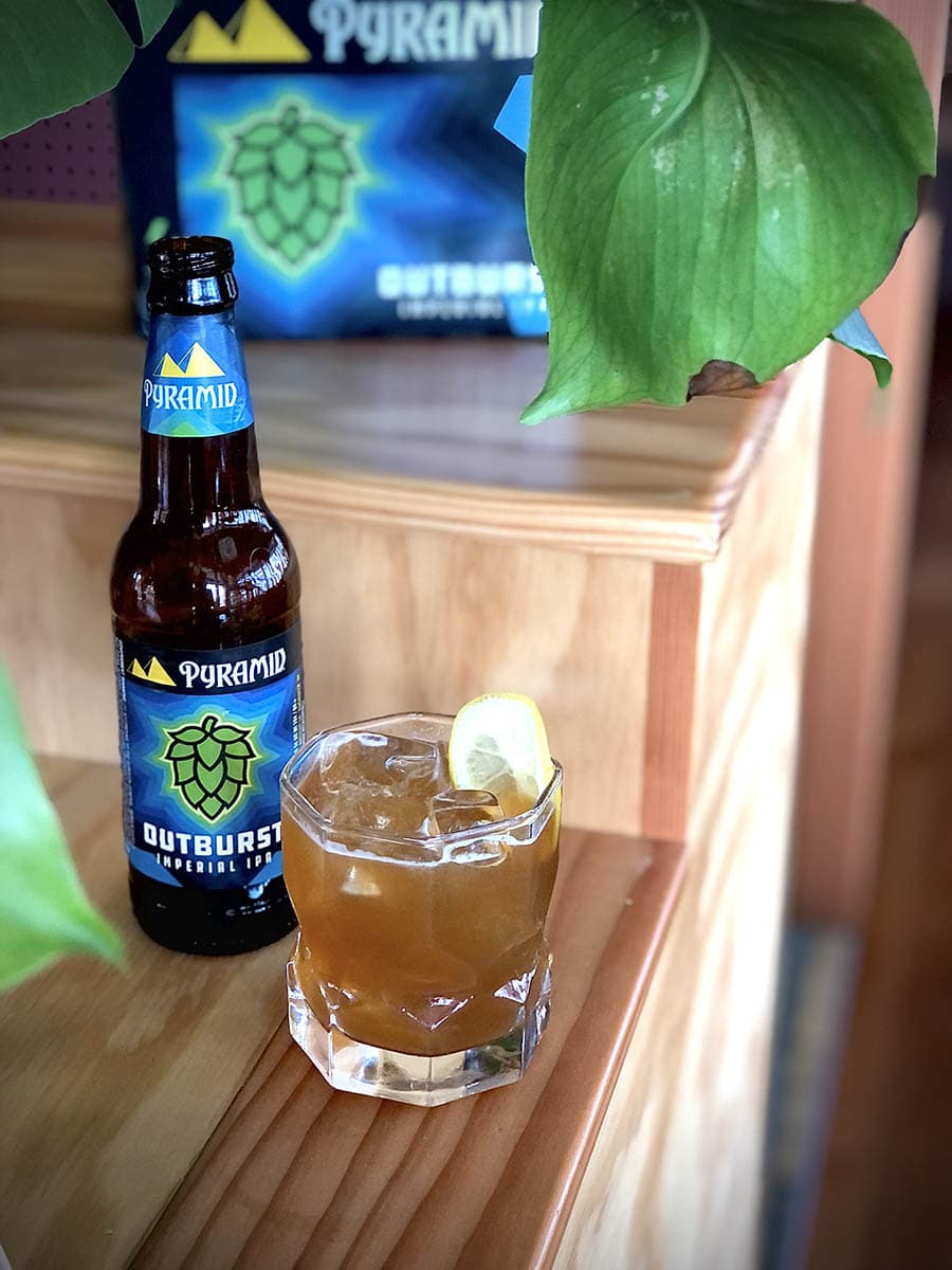 A tumbler full to the brim of the Outburst IPA beer cocktail called the Pacific Summer. The beer, peach brandy, and tea cocktail is positioned next to a bottle of Outburst IPA and some greenery.