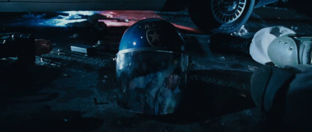 A close up of a discarded police riot helmet, showing the reflection of an approaching zombie hoard