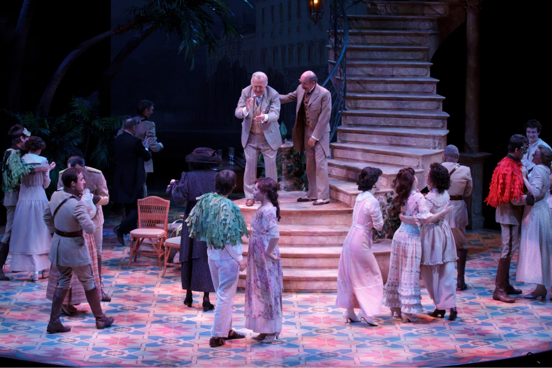Older men laugh on stair landing, surrounded by dancing couples below.