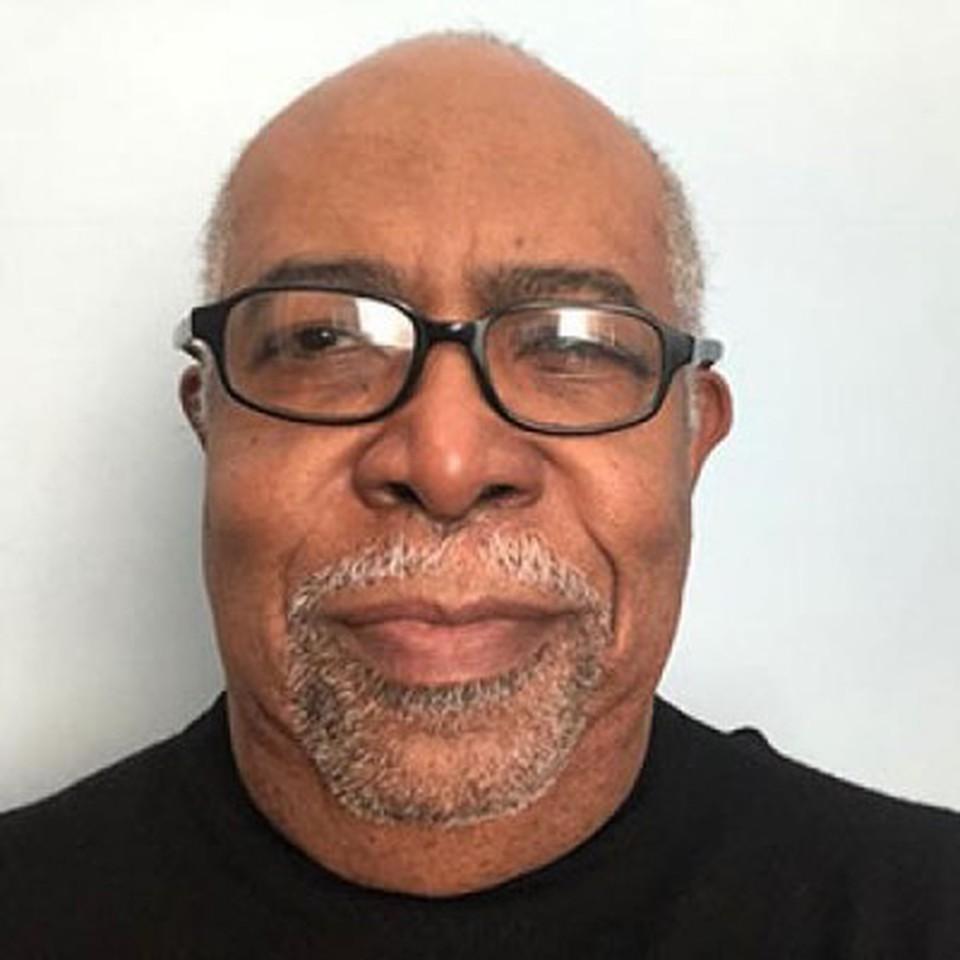 Professor Reginald Parquet - smiling and wearing a black cardigan