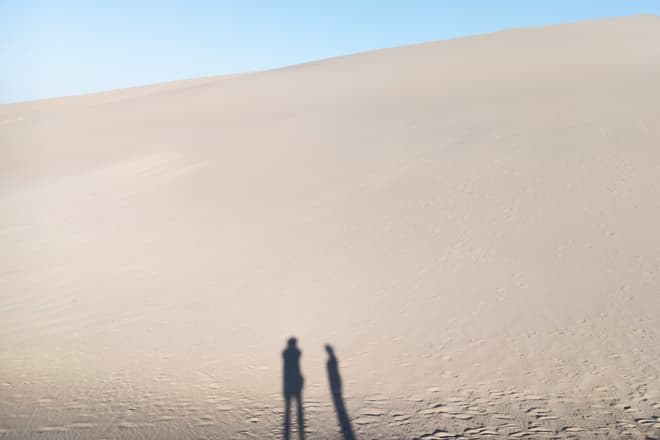 An immense sand dune with the shadows of two people at its base.