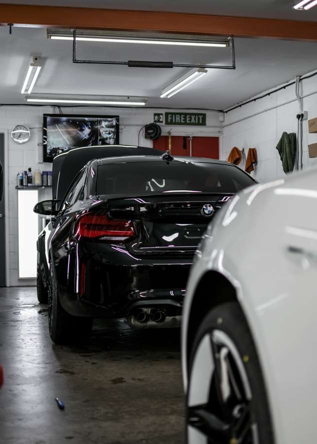 Rear of black BMW M2C during paint protection film (PPF)