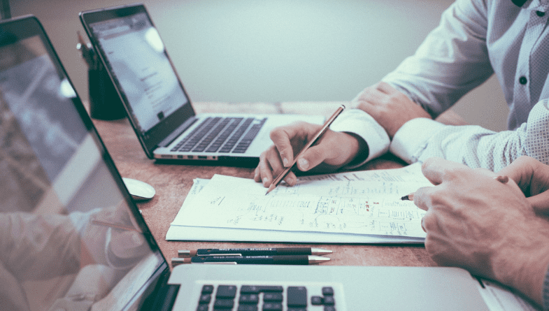 Man sits at desk with tow laptops and paper and files and points with pen to show colleague or client 5 things every business plan must have to be successful as an advisor or business owner including Futrli #businessplan