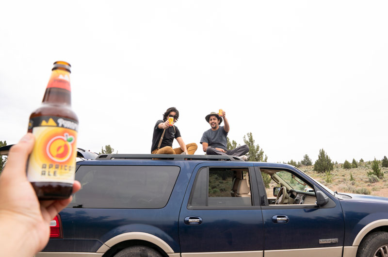Some on holding a bottle of Apricot Ale with two men on top an SUV. They're holding up cans of Blazing Bright.