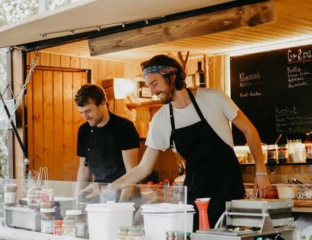 Zwei freundliche Crêpebäcker bei haben gute Laune bei der Crêpezubereitung in einem Crêperie Foodtruck