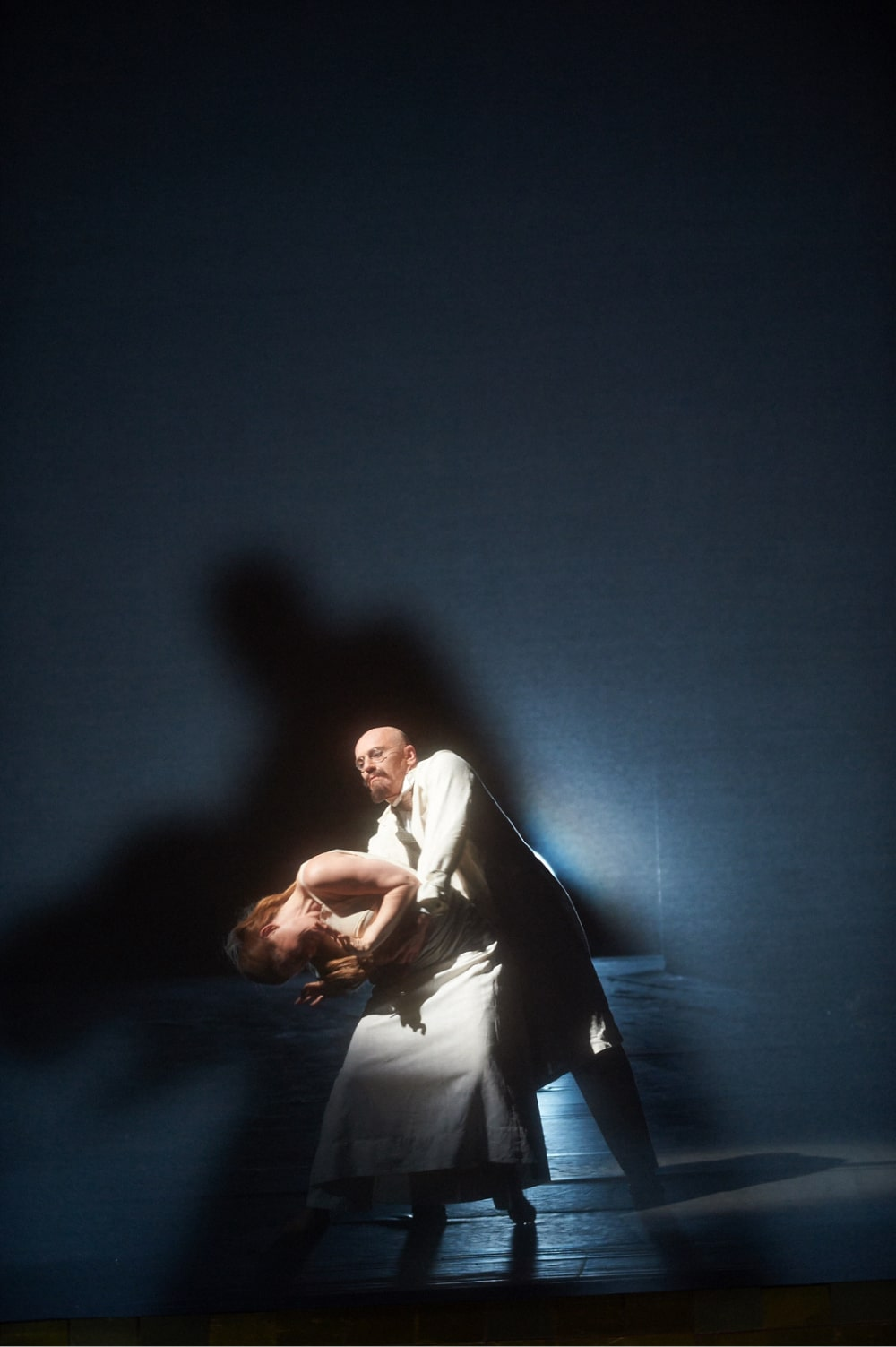 Bald man in lab coat clutches writhing woman in bright light, casting shadows behind.