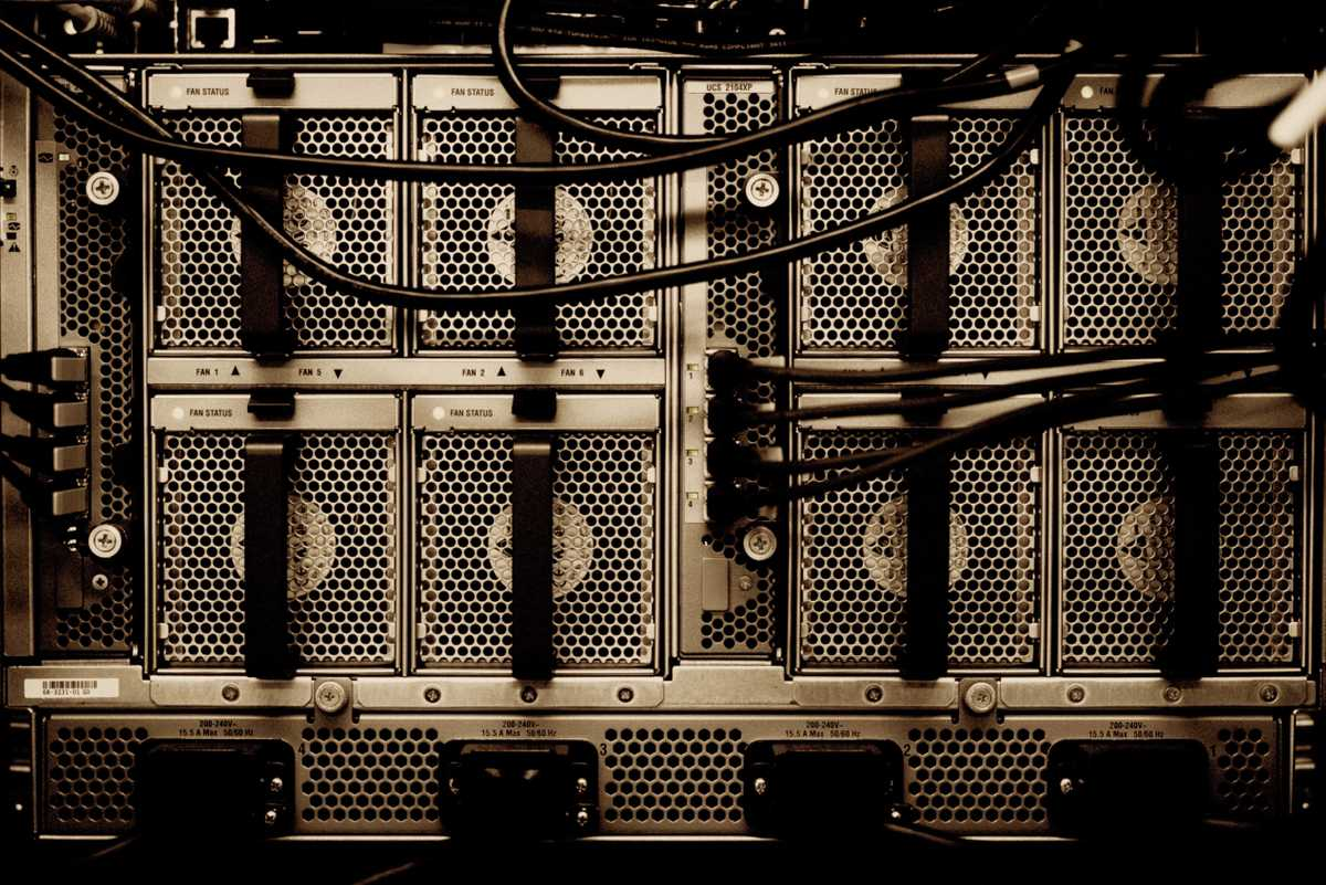 Tangled power and data wires emerge from the rear ports of a server, installed in its rack.