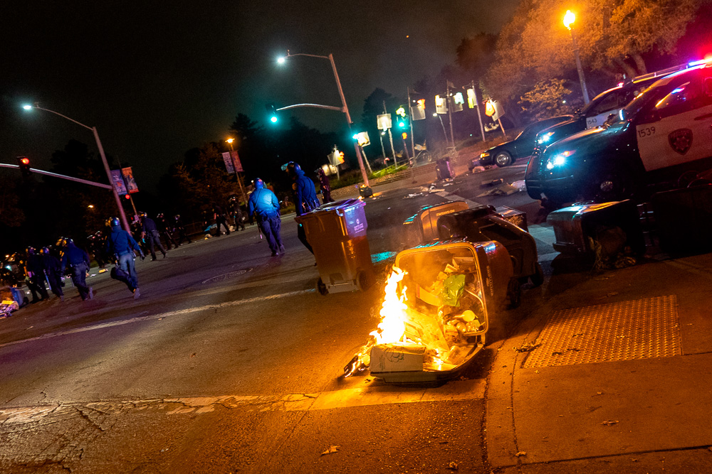 A trash can and its contents burn while police remove blockades from the road during their dispersal of people at the 'Justice for Jacob' protest in Oakland, Calif., August 26, 2020.