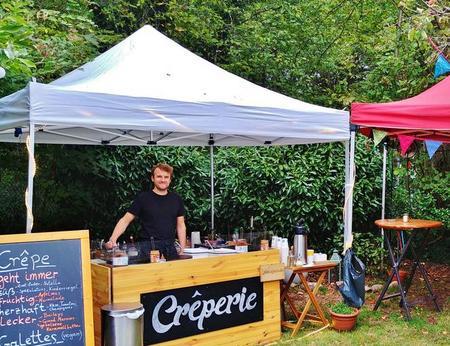 Mobiler Crêpesstand mit natürlicher Holzoptik beim Catering im Außenbereich eines Firmenevents