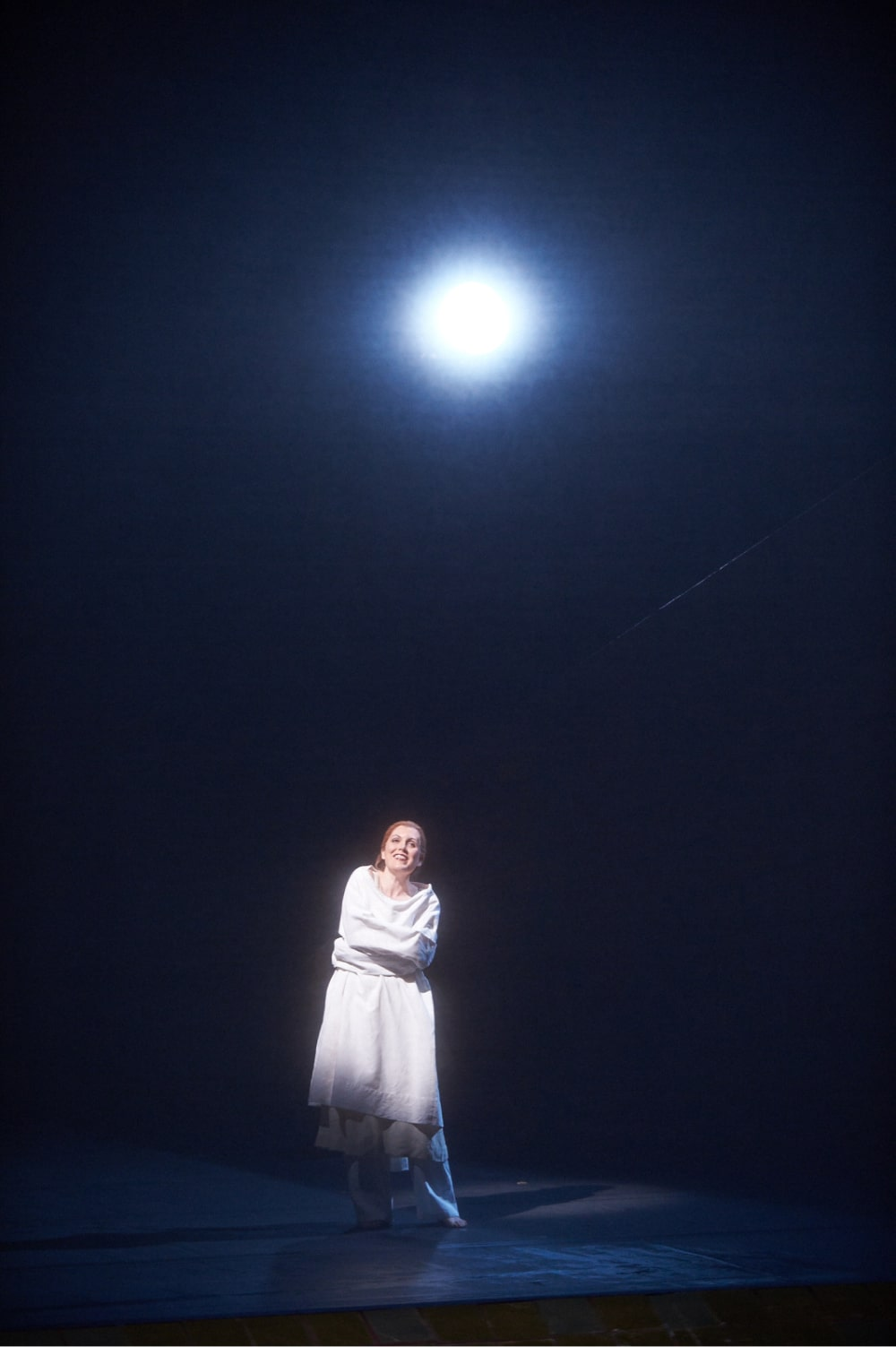 Woman in straight jacket stands smiling in spotlight under gleaming full moon.