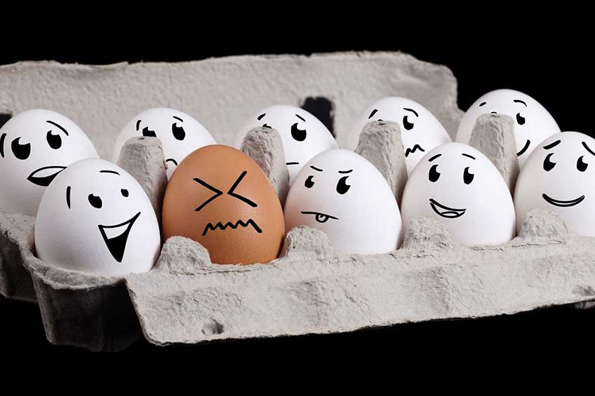 White eggs with faces laughing at brown egg