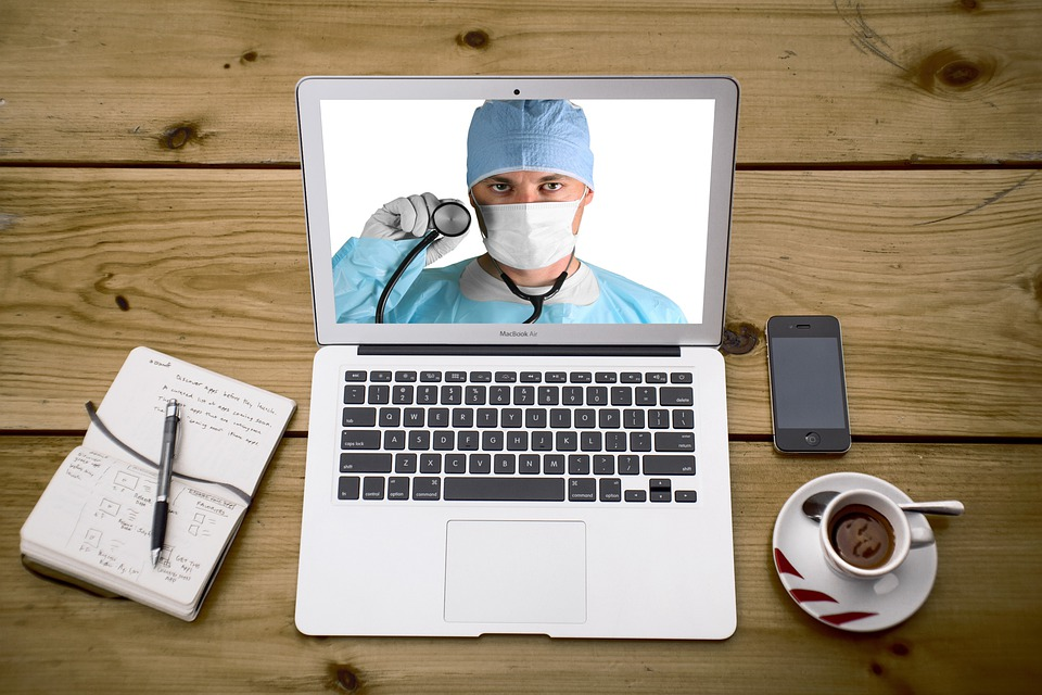 Image of doctor wearing surgical gear on laptop computer screen. A pen and notepad, coffee cup, and cellphone are next to the laptop.