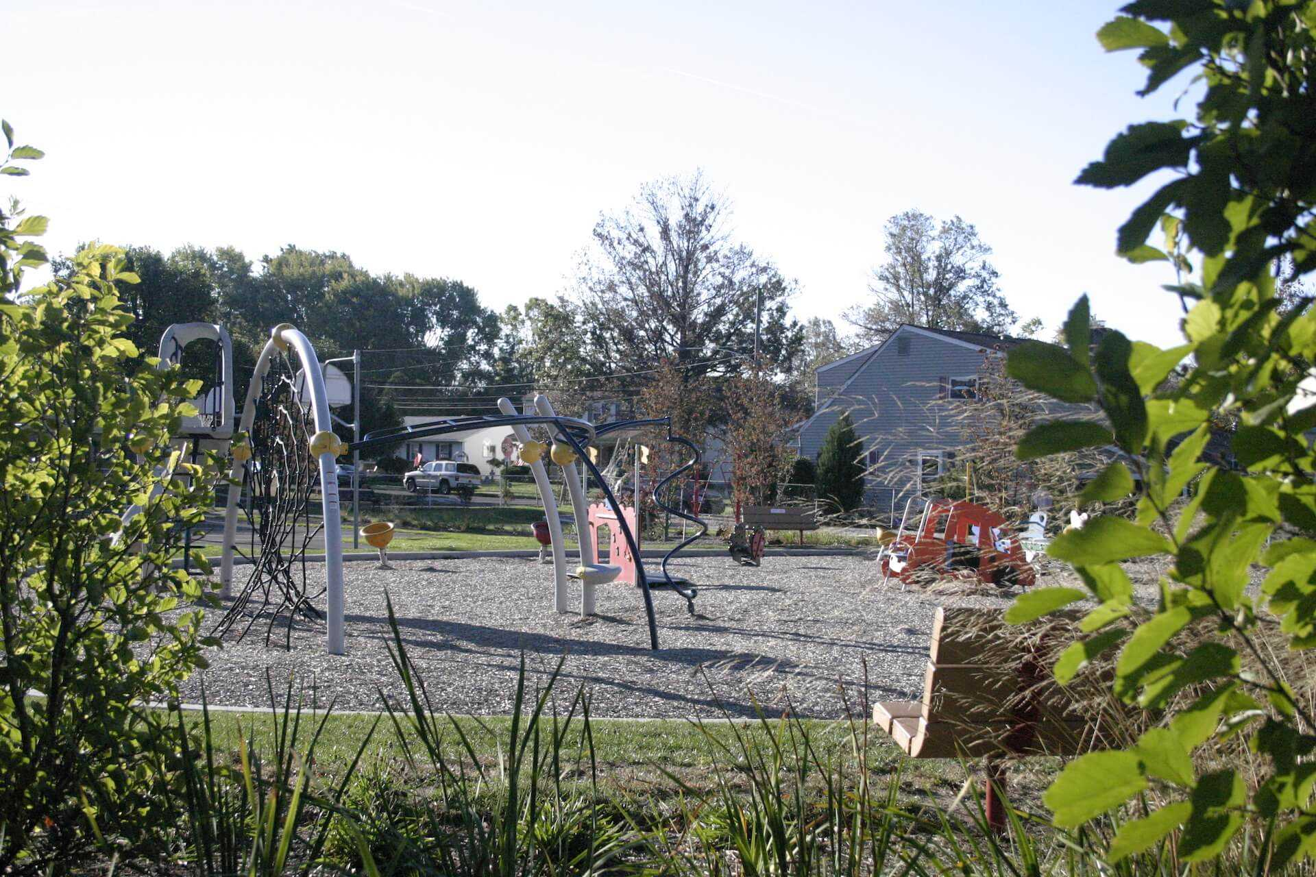 playground behind landscaping and park bench