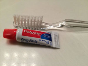 Travel sized toothpaste against toothbrush