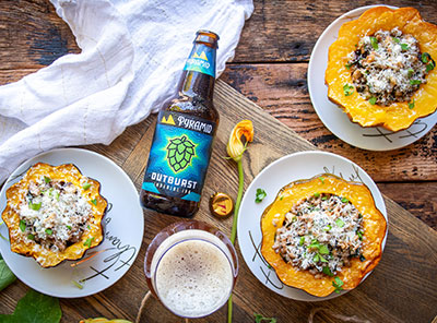 Two acorn squashes filled with sausage and kale on plates surrounded by a bottle of Outburst IPA