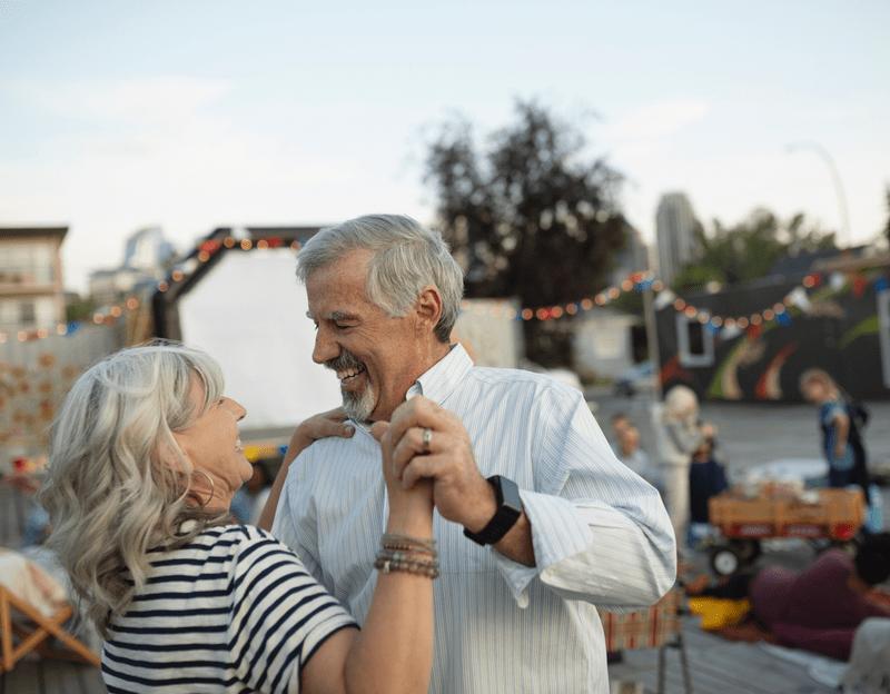 Elderly couple dancing outside.