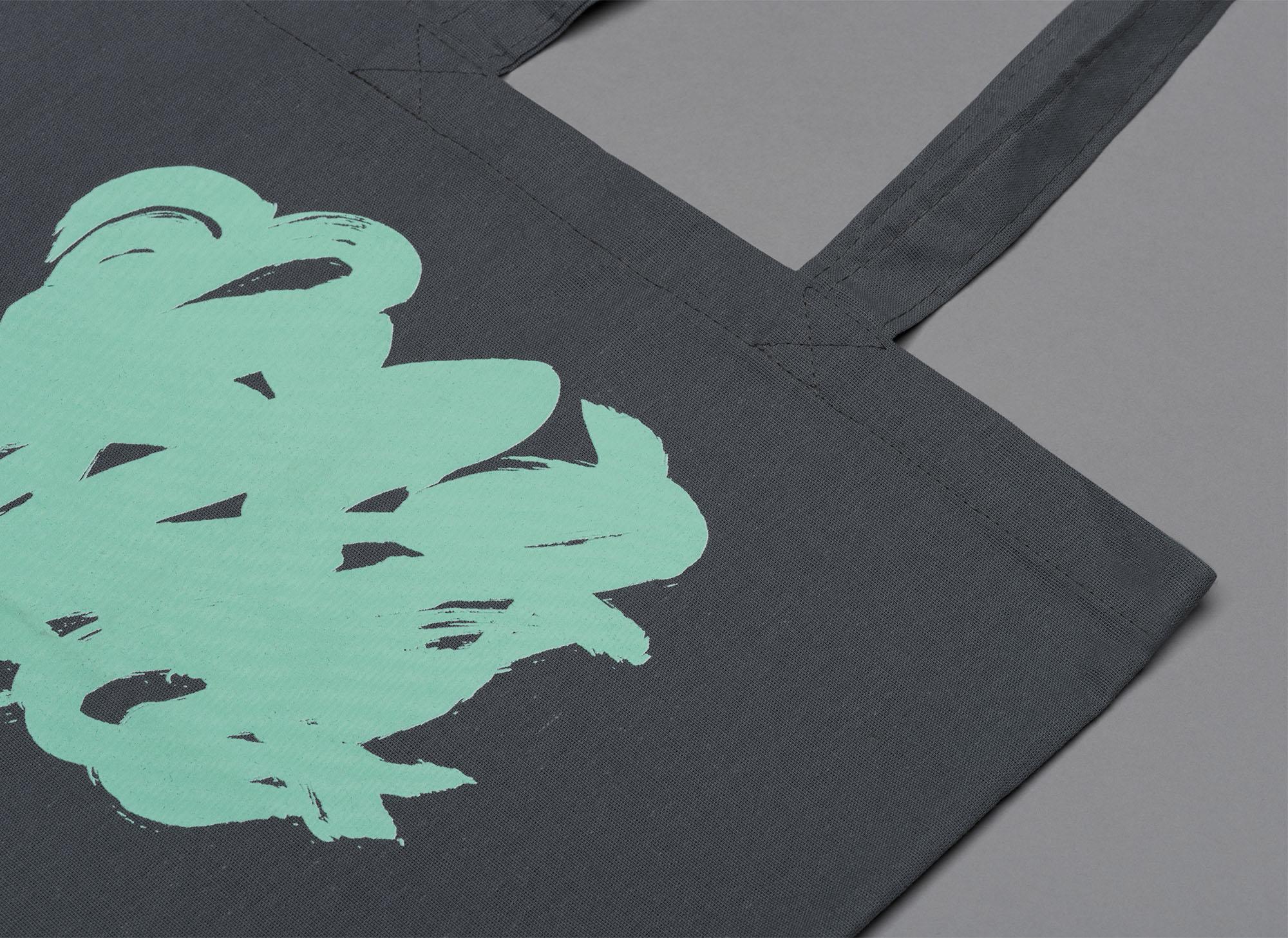 Green swirls screenprinted on a navy blue tote bag