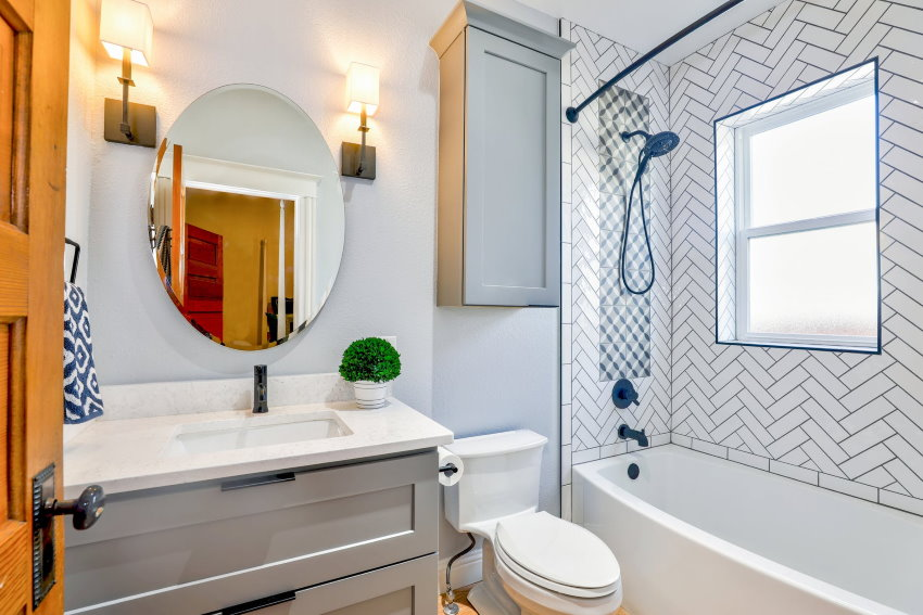 A stylish bathroom with lights around the bathroom mirror and a plant below it, helping to keep the simple mirror stylish and modern, from Christa Grover at Pexels.