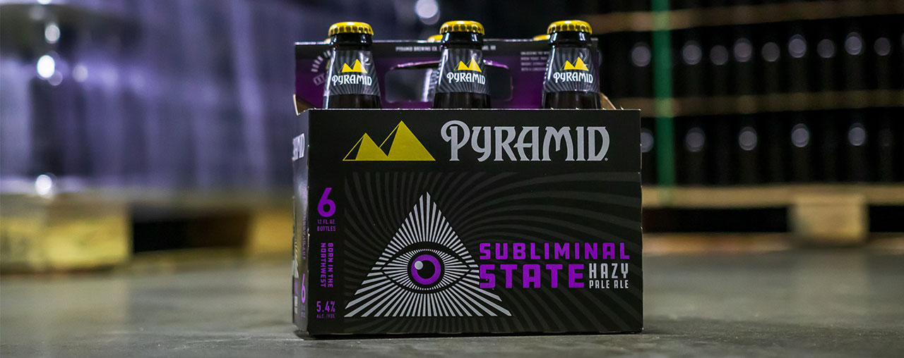 Subliminal State 6-pack on the warehouse floor surounded by palettes