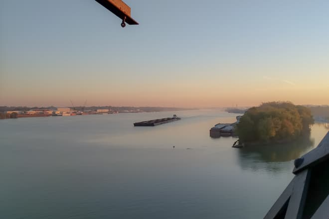 An empty coal barge navigates west along the Ohio River at dawn, slightly closer to the Kentucky side of the river.