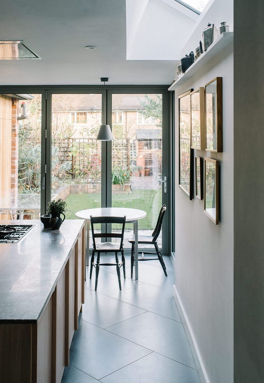 View through Southgrove Road kitchen to the bespoke breakfast table designed and manufactured by From Works of stained light grey birch plywood timber top and stainless steel angle legs.
