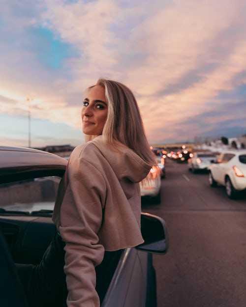 Mujer saliendo por la ventana de un coche