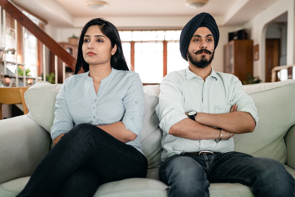 Couple with arms crossed sitting next to each other