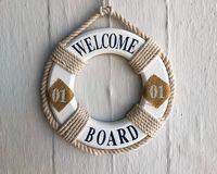 Un salvavidas que dice 'Welcome board' colgado en la pared.
