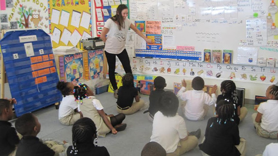 A woman teaching a class of children